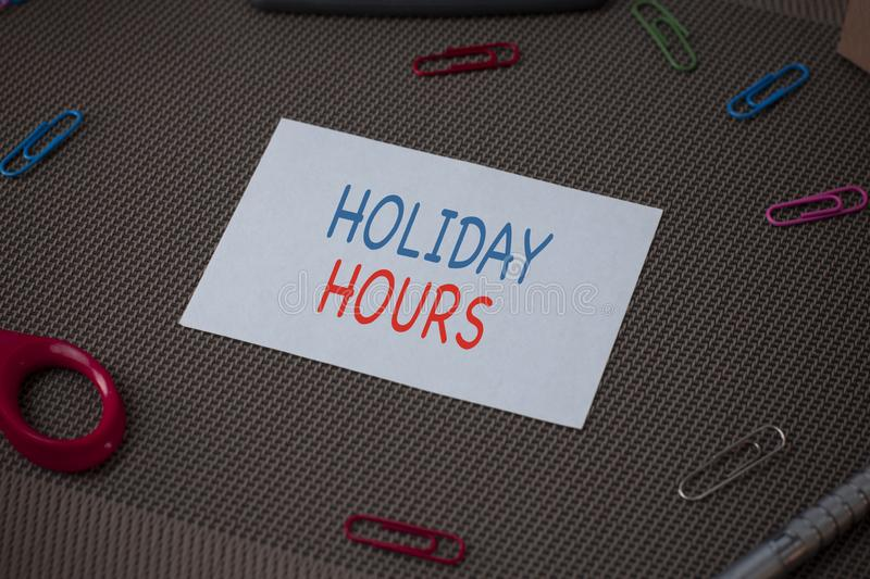 Handwriting text writing Holiday Hours. Concept meaning employee receives twice their normal pay for all hours Scissors. Handwriting text writing Holiday Hours stock photos