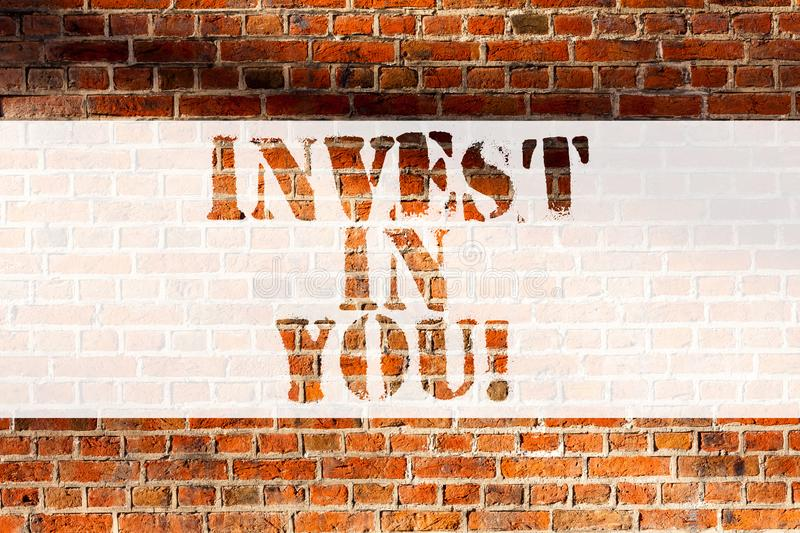 Handwriting text writing Invest In You. Concept meaning Take care of yourself buy things for you Motivation Inspire. Brick Wall art like Graffiti motivational royalty free stock image
