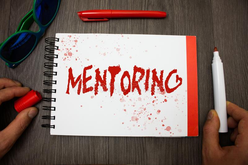 Handwriting text writing Mentoring. Concept meaning To give advice or support to a younger less experienced person Googles glasses stock photography