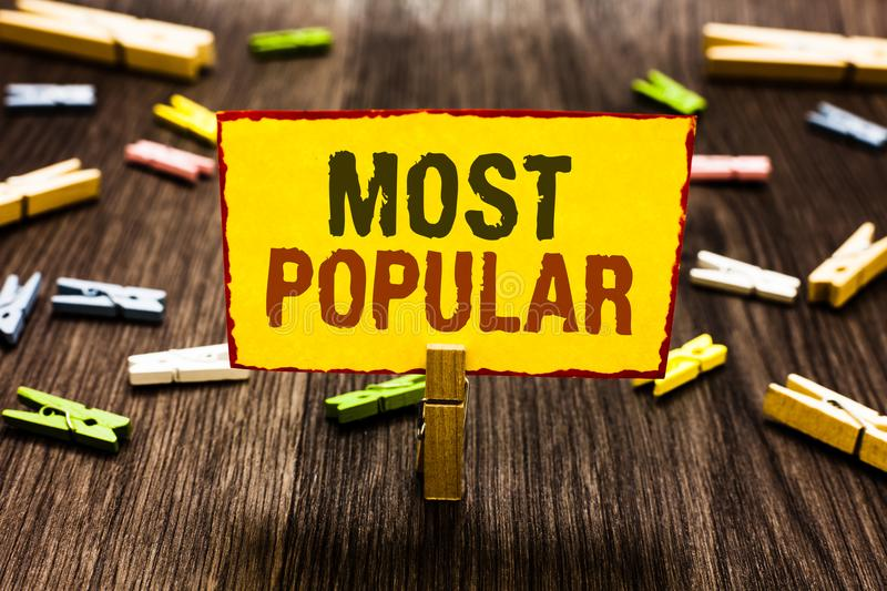 Handwriting text writing Most Popular. Concept meaning Liked Followed Enjoyed by majority of the people in a society Clothespin ho. Lding yellow paper note royalty free stock photography