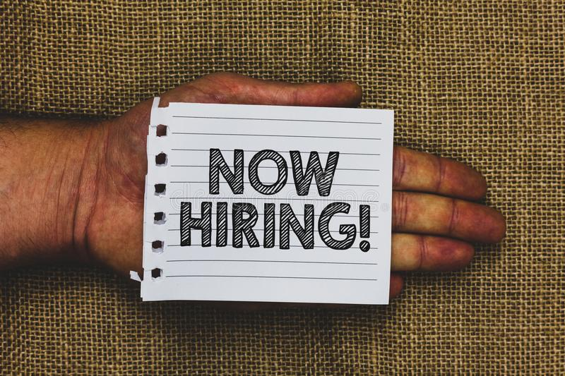 Handwriting text writing Now Hiring. Concept meaning announcing that certain company seeking for new talents Man hand holding piec. E notebook paper jute stock images