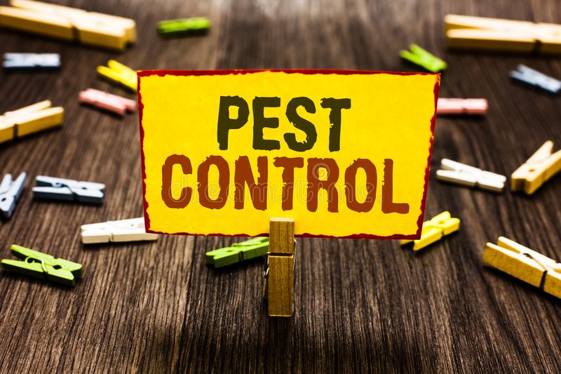 Handwriting text writing Pest Control. Concept meaning Killing destructive insects that attacks crops and livestock Clothespin hol. Ding yellow paper note stock photography