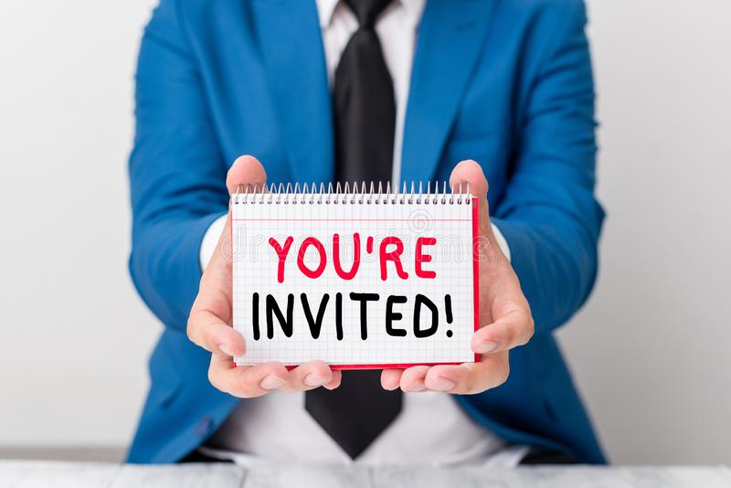 Handwriting text You Re Invited. Concept meaning make a polite friendly request to someone go somewhere Man holds empty. Handwriting text You Re Invited stock images