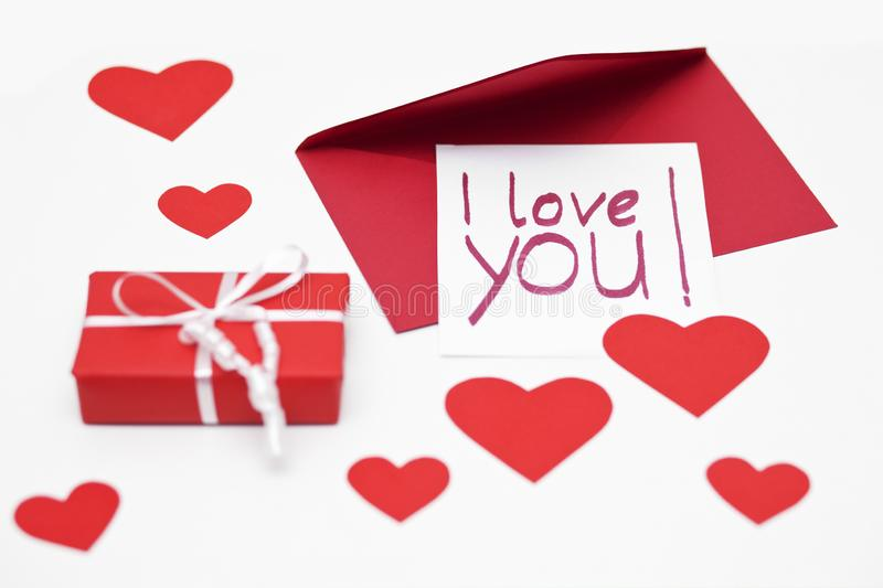 Handwritten I love you - note for Valentine`s Day and a red parcel. royalty free stock photography