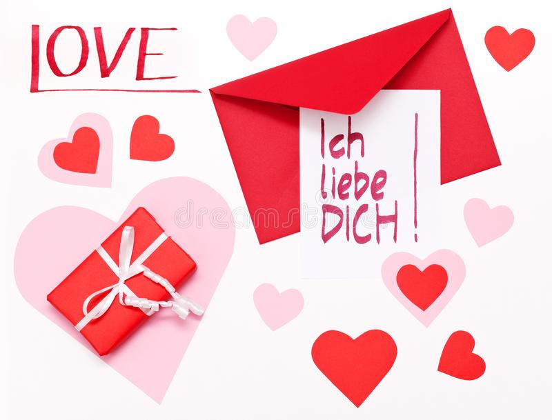 Handwritten Ich-liebe-Dich-note German for Valentine`s Day lying on a red envelope, next to a red parcel, surrounded by red and stock photo