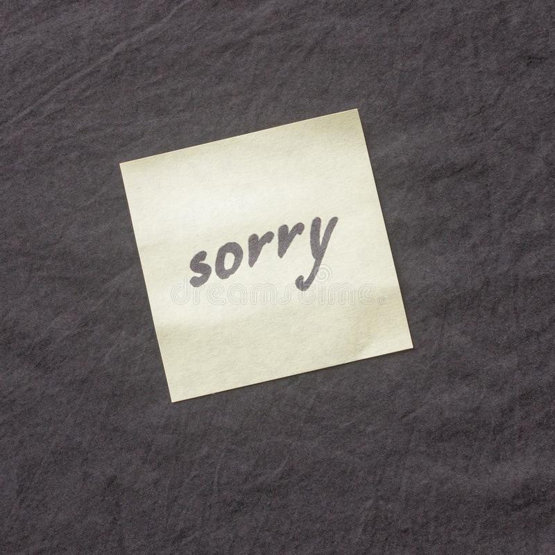 Handwritten note on a dark background. Note of apology- Sorry, p. Lease forgive me stock photo