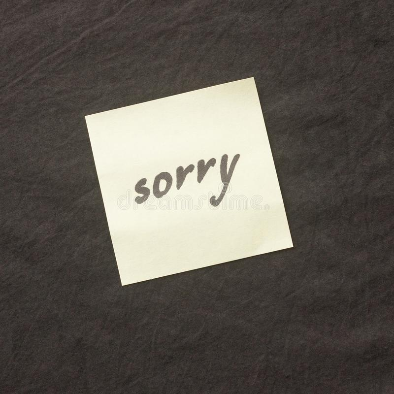 Handwritten note on a dark background. Note of apology- Sorry, p. Lease forgive me stock photos