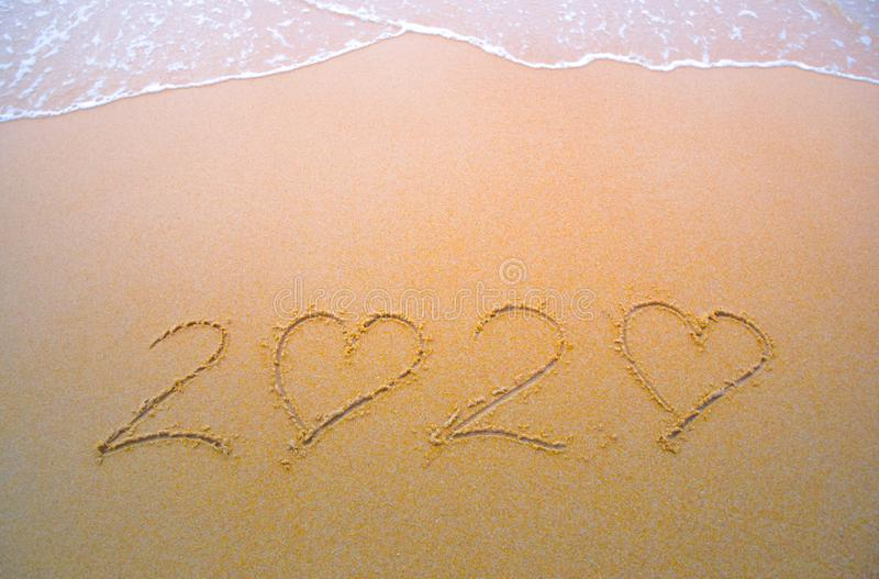 2020 handwritten numeric text on the sand by the beach, Numbers 2020 year on the sand, Happy New Year 2020, Zeros represented by royalty free stock photography