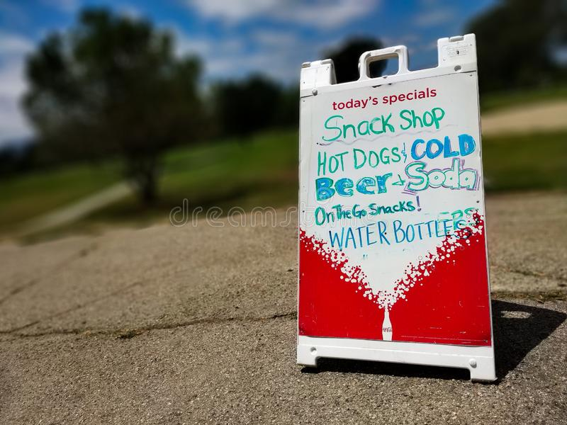 Handwritten sign promoting snacks and refreshments. Beer, soda, water, summer, food, eat, enjoy, sale, golf, outdoors, recreation, hungry, specials royalty free stock image