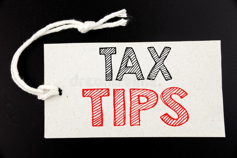 Handwritten text caption showing Tax Tips. Business concept writing for Taxpayer Assistance Refund Reimbursement written on price. Tag paper on black vintage royalty free stock images