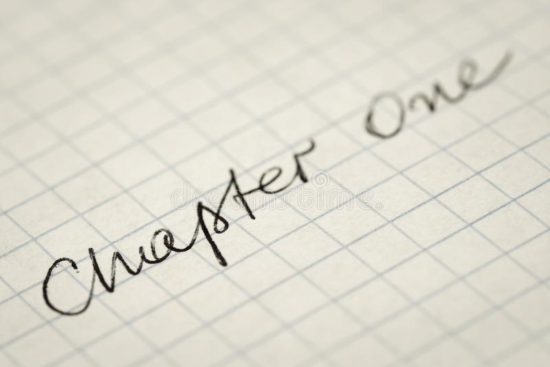 Handwritten text Chapter One on squared paper macro stock photography