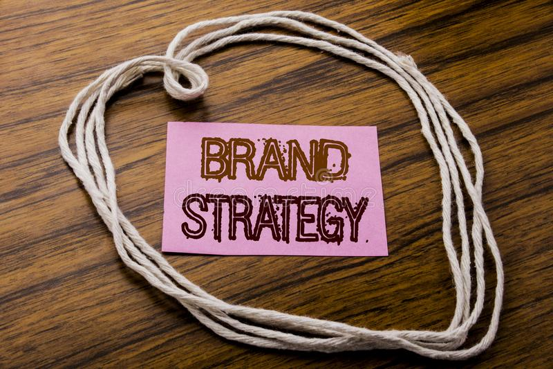 Handwritten text showing Brand Strategy. Business concept for Marketing Idea Plan written on sticky note paper on the dark wooden. Handwritten text showing Brand stock photography