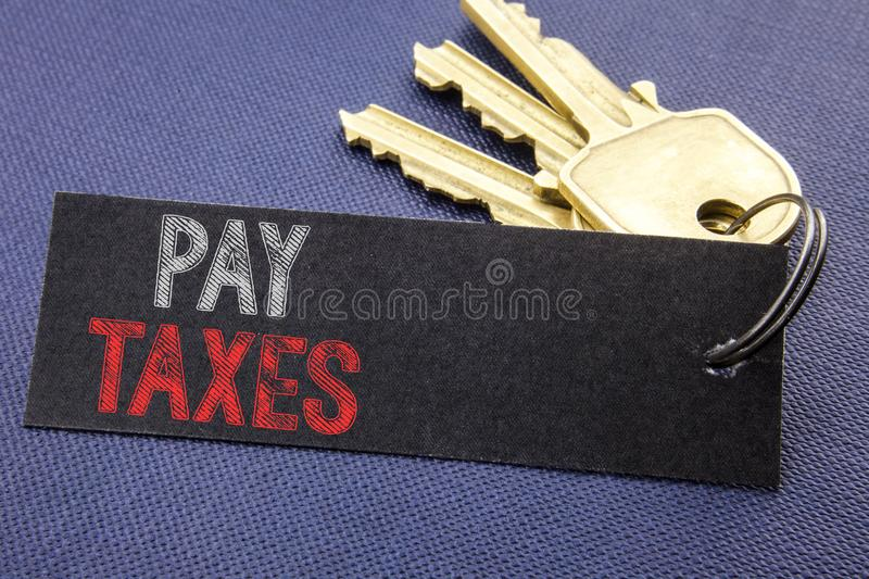Handwritten text showing Pay Taxes. Business concept writing for Taxation Overtax Return Written on note paper attached to the key. Handwritten text showing Pay royalty free stock image