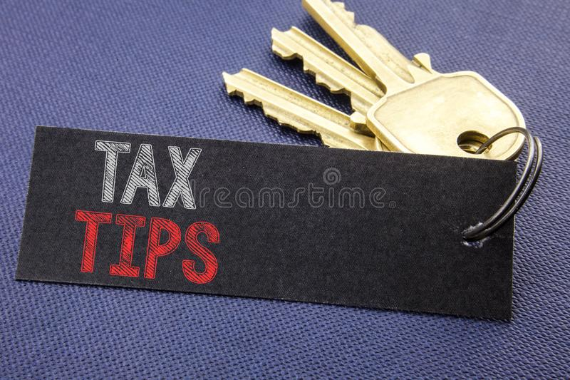 Handwritten text showing Tax Tips. Business concept writing for Tip Forn Taxes Written on note paper attached to the key, black ba. Handwritten text showing Tax royalty free stock photo