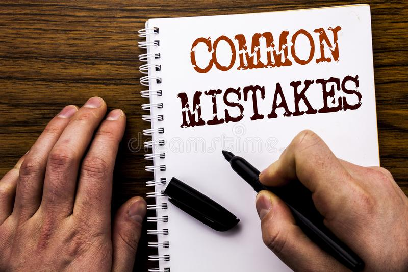 Handwritten text showing word Common Mistakes. Business concept for Common Concept Written on tablet laptop, wooden background wit. Handwritten text showing word royalty free stock photo