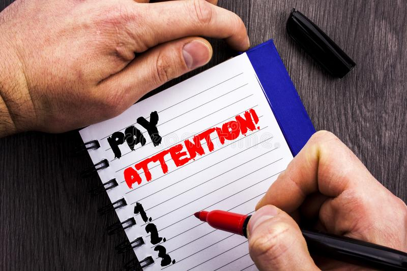 Handwritten text sign showing Pay Attention. Conceptual photo Be Careful Beware Mindful Alarm written on Notebook Book Man Writing. Handwritten text sign showing stock image