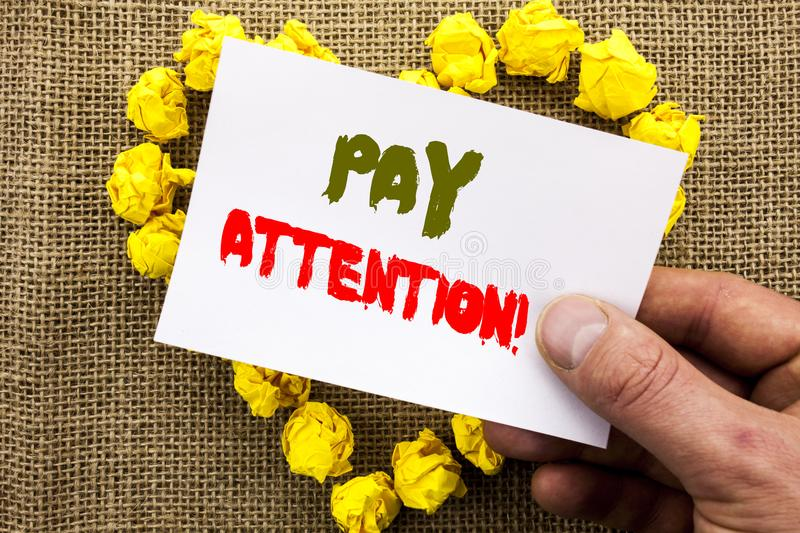 Handwritten text sign showing Pay Attention. Conceptual photo Be Careful Beware Mindful Alarm written on Sticky Note Paper With He. Handwritten text sign showing royalty free stock image