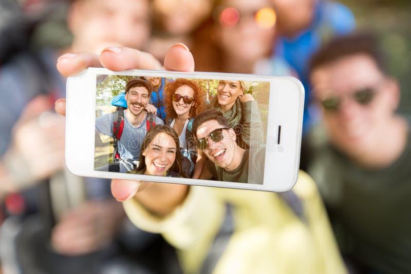 Handy, der Gruppe junge Wanderer fotografiert stockfoto