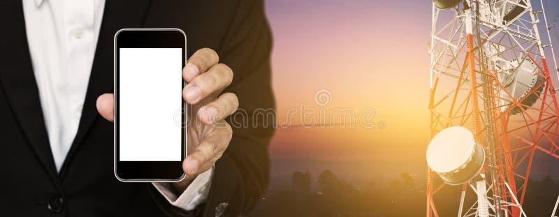 Handy in der Hand des Geschäftsmannes, mit Satellitenschüsseltelekommunikationsnetz auf Telekommunikationsturm bei Sonnenaufgang stockfotografie