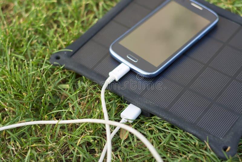 Handy, der mit Solarenergie - Ladegerät auflädt stockfotos