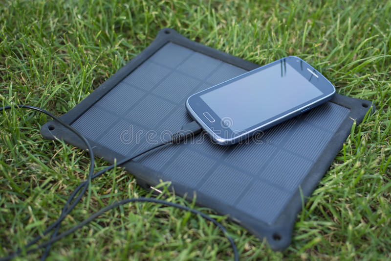 Handy, der mit Solarenergie - Ladegerät auflädt stockbilder