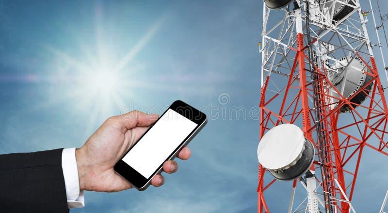 Handy an Hand mit Kopienraum und Telekommunikationsturm mit Satellitenschüsseltelekommunikationsnetz auf blauem Himmel mit Sonne stockfotografie