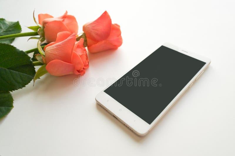 Handy mit Kopienraum, roter Geschenkbox und Rosen auf weißem Hintergrund, stockbild