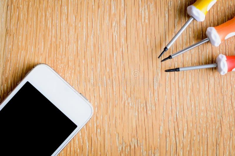Handy mit Werkzeugen des leeren Bildschirms und der Reparatur auf h?lzernem Hintergrund stockfotografie