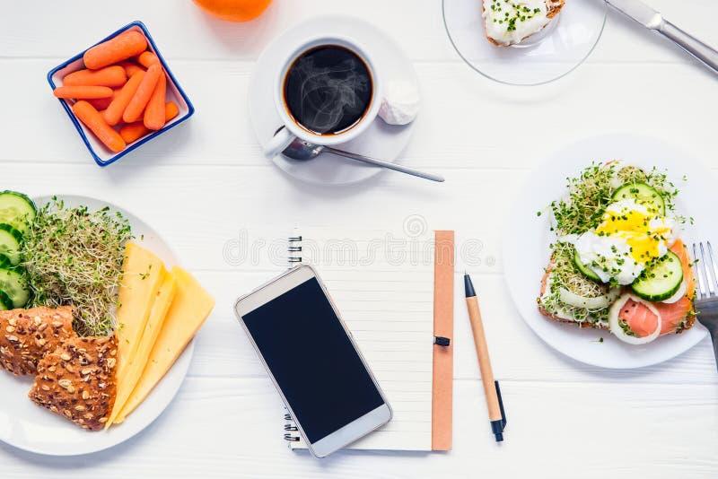 Handy, Planungsnotizbuch und gesunde Frühstück Tagesdiätplanung und Konzept der gesunden Ernährung Sandwich mit Ei Benedict, O lizenzfreie stockfotografie