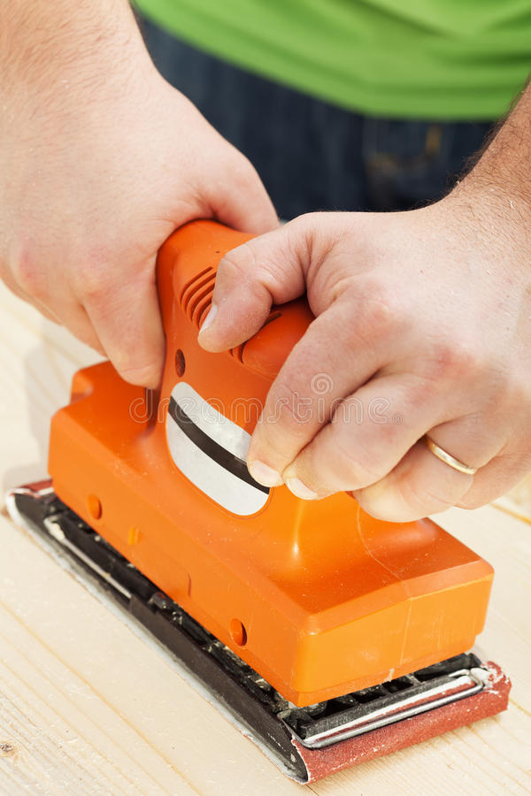 Handy sander machine. Man chiseling wood with sander power tool - closeup royalty free stock photos
