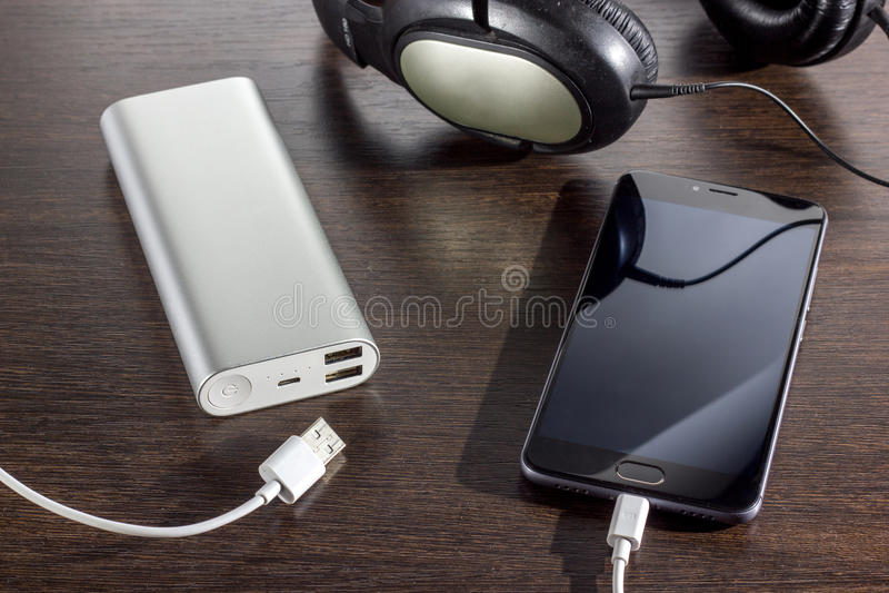 Handy und Energie haben Batterie auf dunklem Hintergrund ein Bankkonto lizenzfreies stockbild