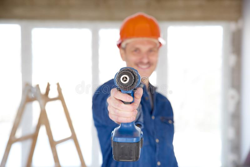 Handy working with drill at construction site stock image
