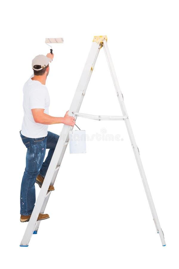 Handyman που αναρριχείται στη σκάλα χρησιμοποιώντας τον κύλινδρο χρωμάτων στοκ φωτογραφία