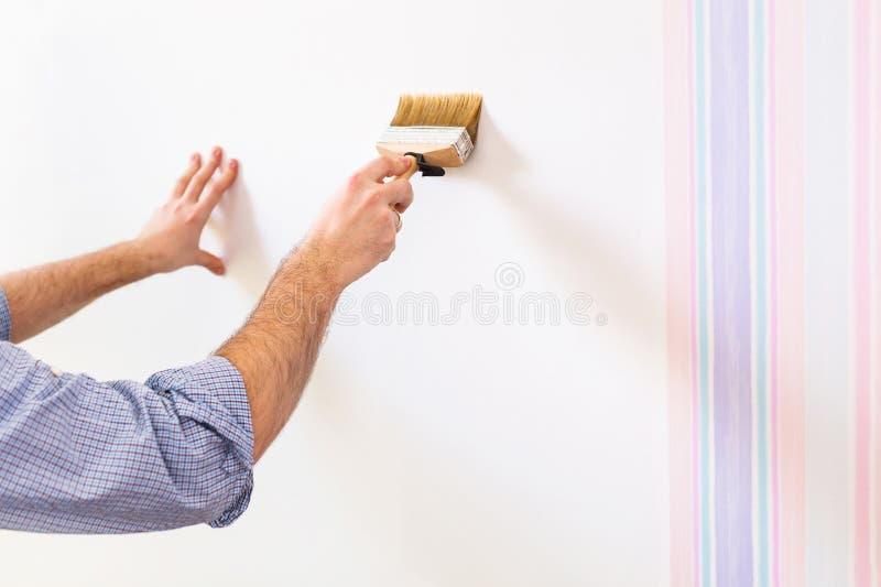 Handyman που βάζει την κόλλα για μια ταπετσαρία στοκ εικόνα