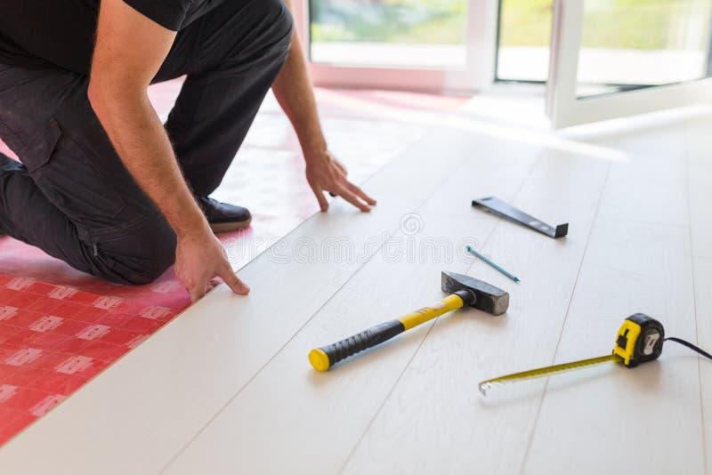 Handyman που εγκαθιστά το νέο τοποθετημένο σε στρώματα ξύλινο πάτωμα στοκ εικόνες