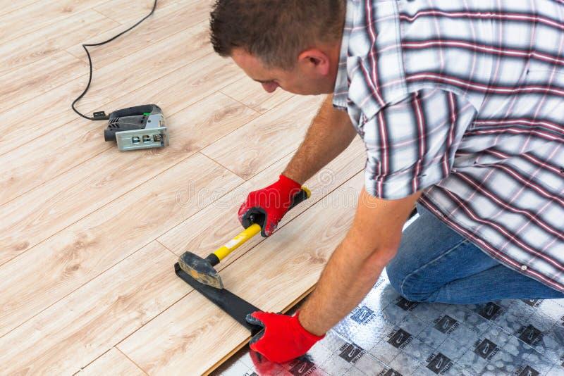 Handyman που εγκαθιστά το νέο τοποθετημένο σε στρώματα πάτωμα στοκ εικόνες