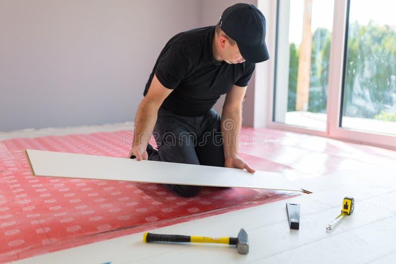 Handyman που εγκαθιστά το νέο τοποθετημένο σε στρώματα πάτωμα στοκ φωτογραφία