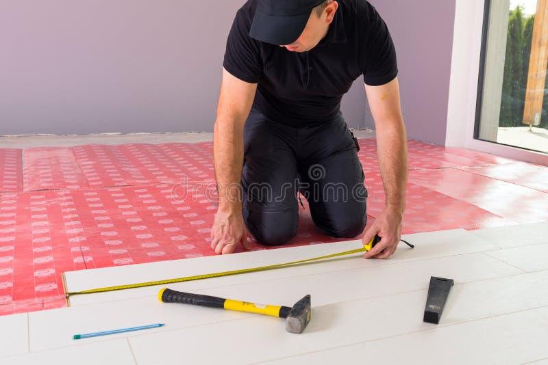 Handyman που εγκαθιστά το νέο τοποθετημένο σε στρώματα πάτωμα στοκ φωτογραφίες με δικαίωμα ελεύθερης χρήσης
