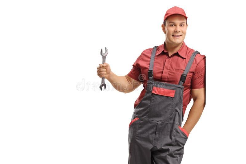 Handyman που κρατά ένα γαλλικό κλειδί και που κλίνει ενάντια σε έναν τοίχο στοκ εικόνα με δικαίωμα ελεύθερης χρήσης