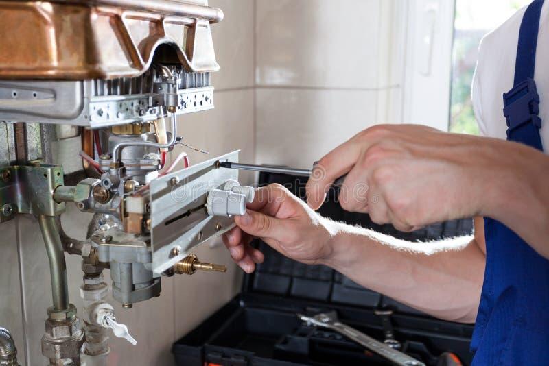 Handyman adjusting gas water heater royalty free stock photography
