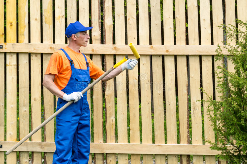 Handyman in blue working uniform checks the condition of paint roller. Standing near the wooden wall royalty free stock photography