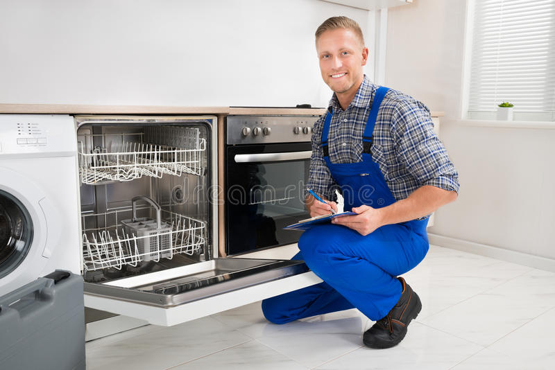 Handyman With Clipboard Looking At Dishwasher. Young Handyman Looking At Dishwasher And Writing On Clipboard stock image