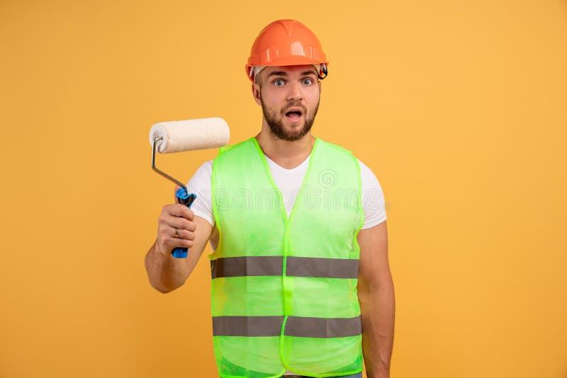 Handyman con rodillo de pintura, pinturas en las paredes de casa, realiza reformas y reparaciones, lleva casco, delantal, ocupado imagen de archivo