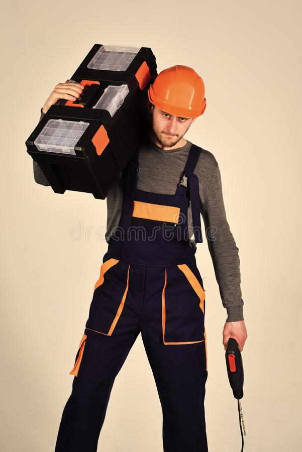 Handyman concept. Man in overall and helmet holds toolbox on shoulder and drill in hand. Strong and attractive repairer stock photos