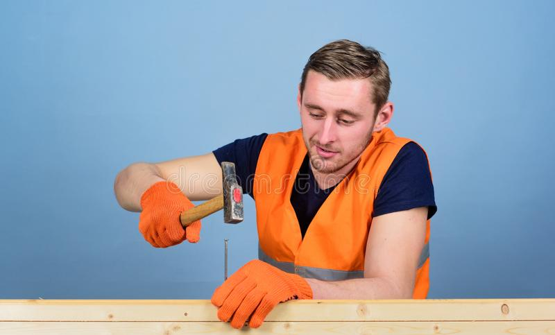 Handyman concept. Man, handyman in working uniform and protective gloves handcrafting with hammer, light blue background royalty free stock photos
