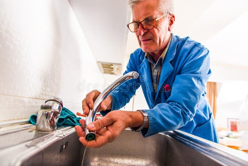 Handyman consertando a torneira da cozinha fotos de stock royalty free