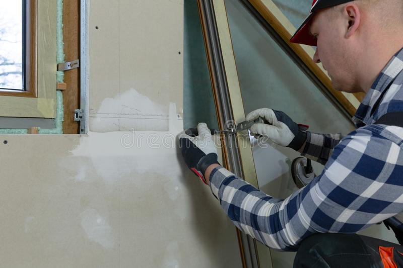 Handyman, construction man installing PVC window in a new insulated and filled dry wall attic royalty free stock images
