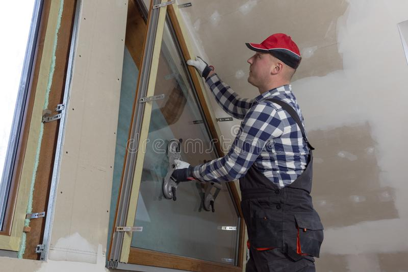 Handyman, construction man installing PVC window in a new insulated and filled dry wall attic stock image