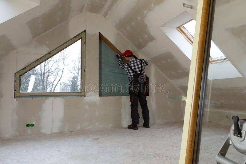 Handyman, construction man installing PVC window in a new insulated and filled dry wall attic royalty free stock photo