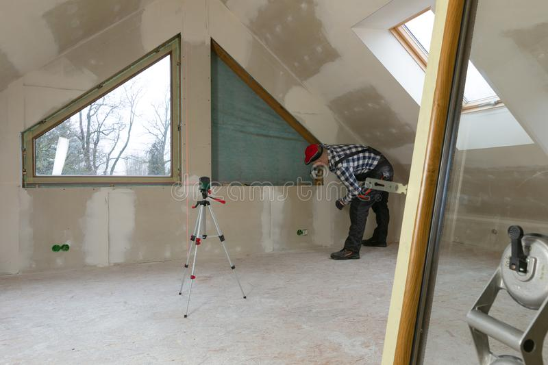 Handyman, construction man installing PVC window in a new insulated and filled dry wall attic stock photos
